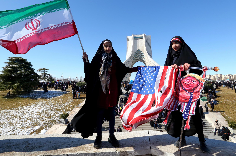إيرانية تلوح بعلم وطني وأخرى تحمل علما أمريكيا ممزقا خلال احتفالات الذكرى الـ41 للثورة الإسلامية في ساحة أزادي بطهران في 11 شباط/فبراير 2020