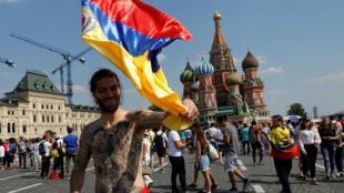 Un partidario de la selección colombiana de fútbol ondea una bandera frente a la Catedral de San Basilio en la Plaza Roja en Moscú, Rusia, el 18 de junio de 2018.