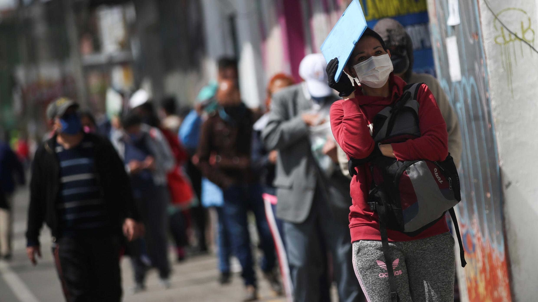 Personas con mascarillas se alinean afuera de un banco en medio del brote de coronavirus en Bogotá, Colombia, el 1 de julio de 2020.