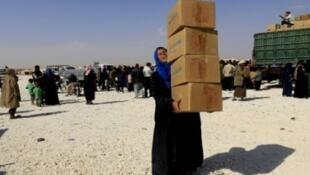 لاجئة سورية تحمل صناديق مساعدات في مخيم للاجئين الهاربين من البوكمال ودير الزور والميادين في 14 تشرين الأول/أكتوبر في بلدة العريشة في محافظة الحسكة السورية