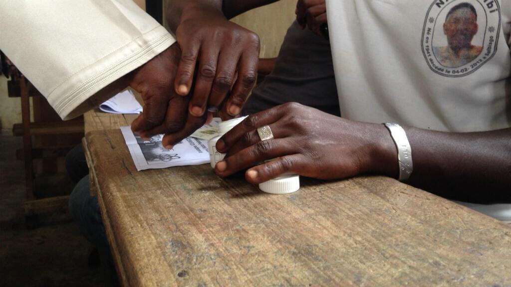 Un électeur ivoirien plonge son doigt dans l'encrier après avoir voté - un procédé destiné à éviter qu'une même personne vote plusieurs fois.