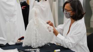 Une couturière travaille sur la robe de mariée haute couture dans les ateliers Dior, le 4 juillet 2020