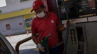 عامل في محطة وقود يضع قناعا وقفازات في كراكاس في 16 آذار/مارس 2020