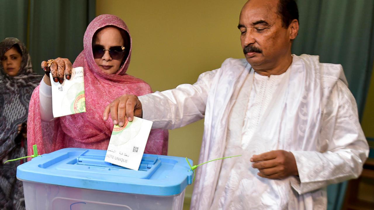 الرئيس الموريتاني محمد ولد عبد العزيز وزوجته تكبير بنت أحمد يدليان بصوتيهما في مركز اقتراع في نواكشوط في 22 يونيو/حزيران 2019.