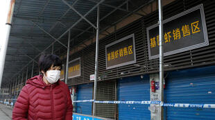 A woman walks in front of the closed Huanan wholesale seafood market, where health authorities say a man who died from a respiratory illness had purchased goods from, in the city of Wuhan, Hubei province, file photograph taken on January 12, 2020.