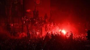 Des supporters de Liverpool célèbrent le sacre de leur équipe à côté du stade d'Anfield le 25 juin 2020