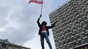 متظاهر يرفع العلم اللبناني خلال تظاهرة قبالة مؤسسة كهرباء لبنان في بيروت، 11 كانون الثاني/يناير 2020