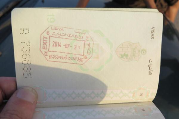 Un travailleur tunisien montre son passeport pour montrer qu'il a quitté la Libye seulement la veille.