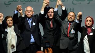 Le nouveau Premier ministre du gouvernement d'union libyen, Fayez al-Sarraj, entouré du vice- président du Congrès général national (CGN), Saleh el-Makhzoum, et du président de la chambre des représentants de Tobrouk, Mohammed Ali Shoeb, après la signature de l'accord sur un gouvernement d'union, le 17 décembre 2015, à Skhirat, au Maroc.