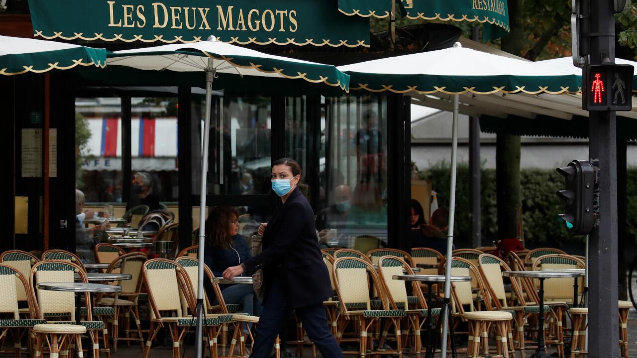 Una mujer con una mascarilla pasa por la cafetería y restaurante Les Deux Magots en París, tras el anuncio de las nuevas restricciones de Covid por parte de las autoridades de París, el 5 de octubre de 2020.