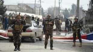 Des agents de sécurité afghans patrouillent dans la zone après l'attentat-suicide survenu contre un convoi militaire, à Kaboul, le 2 mars 2018.
