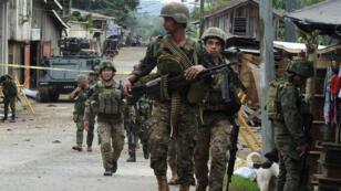 Miembros del Ejército filipino vigilan las inmediaciones de una base militar, mientras adelantan una investigación por un atentado con explosivos, el 28 de junio de 2019, en la isla de Jolo, sur de Filipinas.