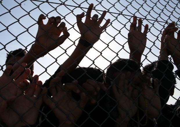 Les mains crochetées aux grillages, les détenus interpellent tous ceux qui passent sur le chemin de terre qui longe leur prison à ciel ouvert.