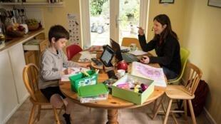 El niño de seis años Leo hace las tareas indicadas en la web de su escuela infantil mientras su madre, Moira, empleada de la administración regional, teletrabaja junto a él en su casa de Marsden, pueblo al norte de Inglaterra, el 15 de mayo de 2020