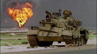 An abandoned Iraqi Soviet-made T-62 tank sits in the Kuwaiti desert as an oil well burns in the background, on April 2, 1991