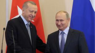 Le président russe, Vladimir Poutine, serre la main du président turc, Recep Tayyip Erdogan, lors de leur conférence de presse conjointe à la suite des pourparlers russo-turcs dans la station balnéaire de Sochi, en Russie, le 22 octobre 2019.