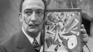 Salvador Dali montre un tableau qu'il vient d'achever au zoo de Vincennes, le 30 avril 1955.