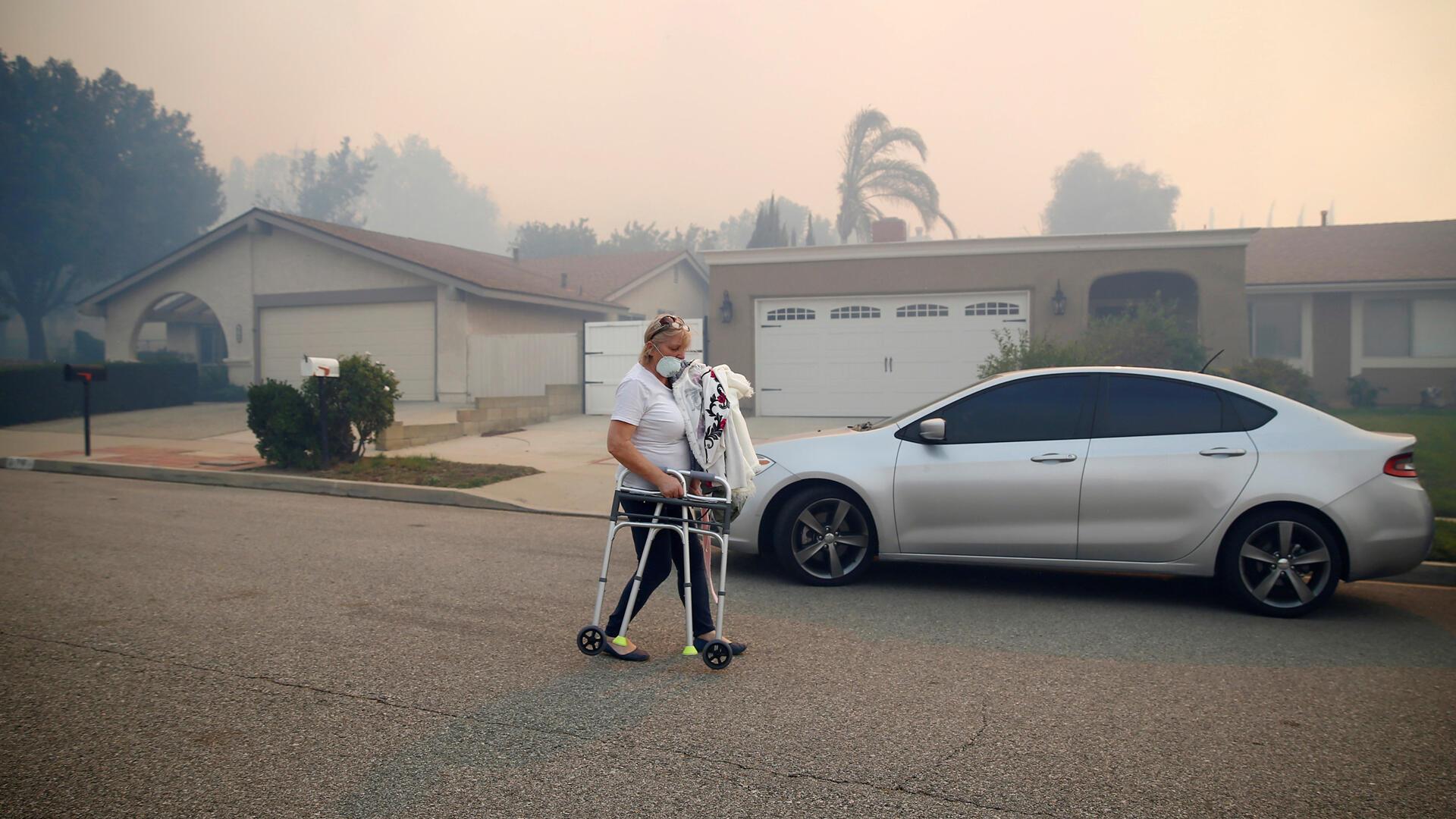Una mujer con un caminador se desplaza con dificultad en Simi Valley, donde el Incendio Peak hace estragos.