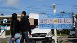 Una pareja pasa frente a una bandera argentina que cuelga en la entrada de la Base Naval Argentina donde partió el submarino desaparecido ARA San Juan, en Mar del Plata. Noviembre 19, 2017