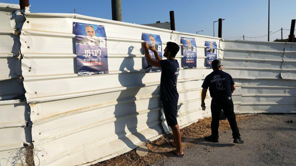 Los partidarios del partido Yisrael Beitenu de Avigdor Lieberman, cuelgan los carteles de la campaña electoral del partido cerca de una mesa electoral en el asentamiento israelí de Nokdim en la Cisjordania ocupada, el 17 de septiembre de 2019.