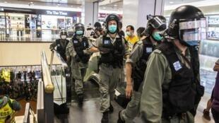 عناصر شرطة مكافحة الشغب يضعون أقنعة واقية ويتعقبون متظاهرين في أحد مراكز التسوق في هونغ كونغ، في 9 أيار/مايو 2020