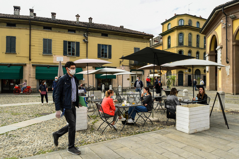 Residentes de Codogno toman una copa en la terraza de un café mientras Italia alivia su encierro para frenar la propagación del coronavirus.