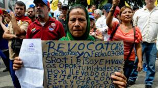 Une manifestante vénézuélienne, samedi 14 mai 2016 à Caracas, porte une pancarte demandant la tenue du référendum sur la révocation du président Maduro.