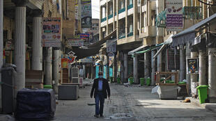 An Iraqi man walks past closed shops in Baghdad on February 19, 2021, as authorities re-imposed partial lockdown measures until early March following a new coronavirus surge