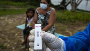 موظف صحي حكومي يعرض نتيجة فحص كوفيد-19 في جزيرة ماراخو في ولاية بارا في البرازيل في 1 حزيران/يونيو 2020.