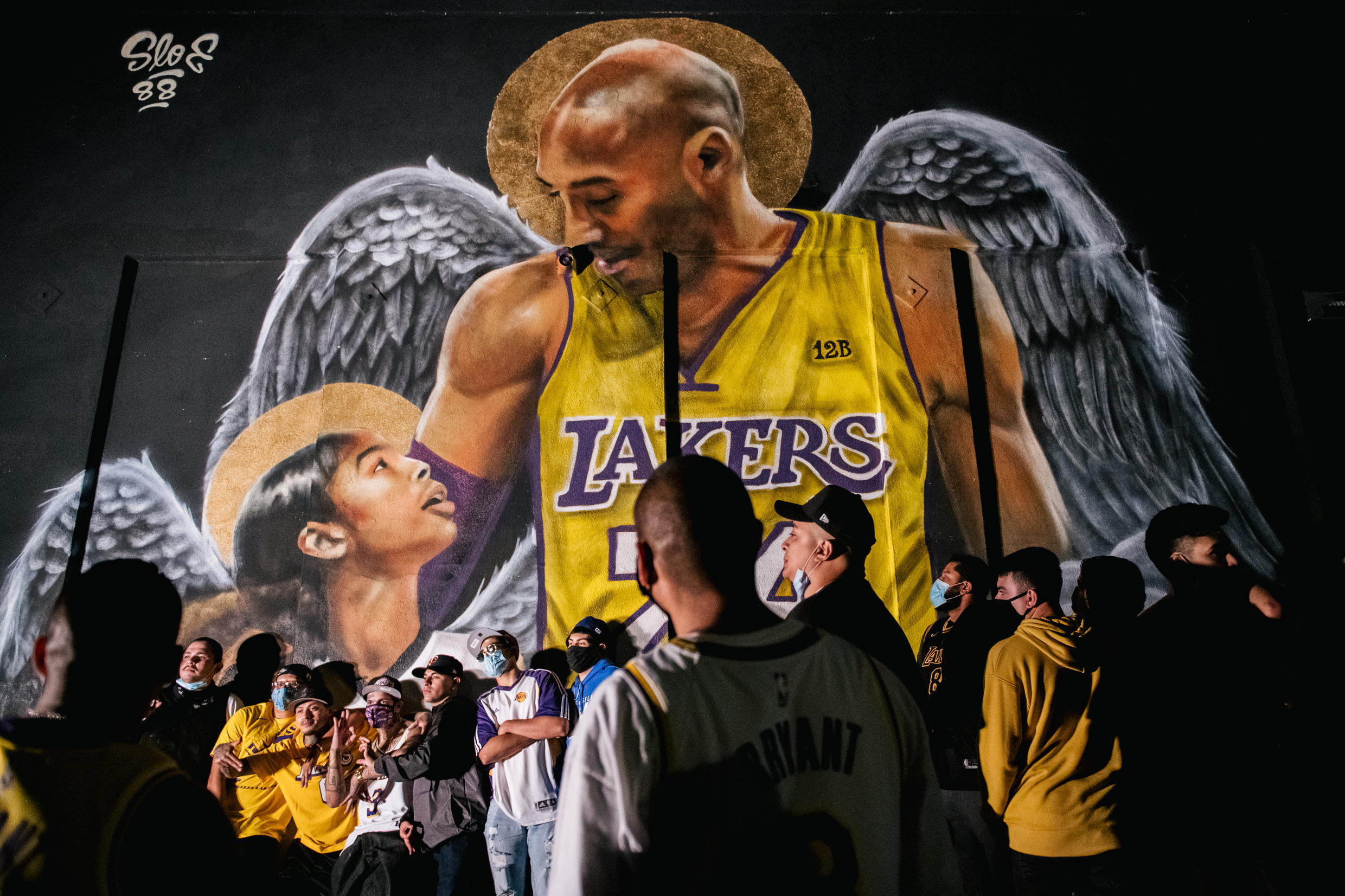 Lakers fans stand in front of a mural of Kobe Bryant and his daughter Gianna Bryant on October 11, 2020, in Los Angeles, California, after the team defeated the Miami Heat in Game 6 of the NBA Finals.