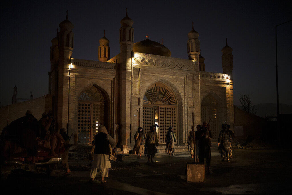 Taliban fighters walk to the entrance of the Eidgah Mosque after an explosion in Kabul, Afghanistan, on Sunday, October 3, 2021.