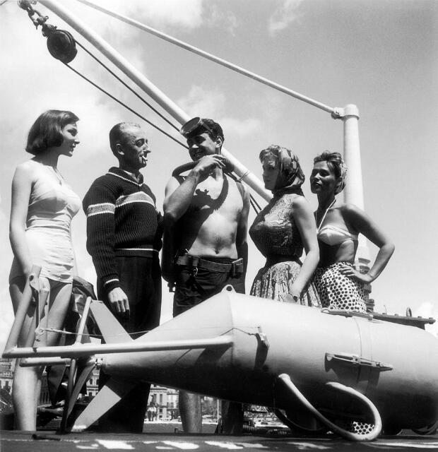 """Le commandant Cousteau entouré du plongeur Albert Falco et de l'actrice Isabelle Corey sur le pont de la Calypso, lors d'une fête organisée à bord pendant le festival de Cannes de 1956. Cette année-là, """"Le Monde du Silence"""" remportait la Palme d'Or."""
