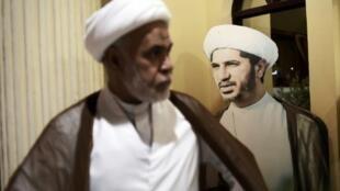 رجل دين بحريني يمر بالقرب من صورة لزعيم المعارضة الشيعية الشيخ علي سلمان خلال احتجاج في 29 مايو 2016 على توقيفه