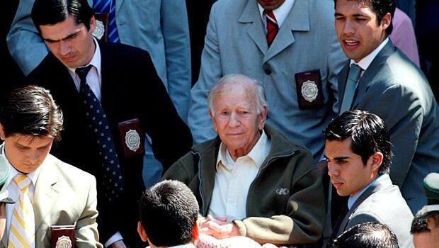 El exlíder de la secta secreta Colonia Dignidad, Paul Schaefer (C), en una silla de ruedas frente a la estación de policía de Interpol después de un interrogatorio en Santiago el 14 de marzo de 2005.