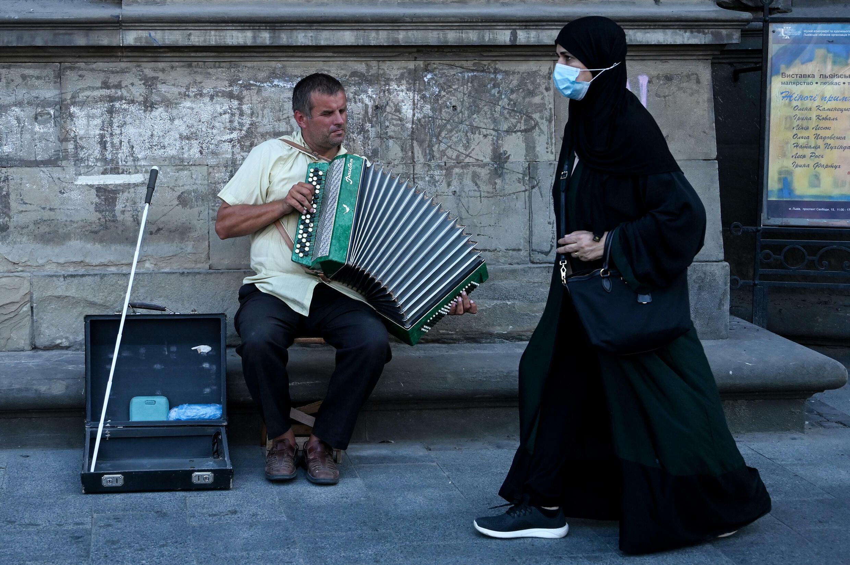 سائحون من دول الخليج يمرون بموسيقي شوارع في 14 أغسطس 2021 في إلفيف ، أوكرانيا.