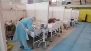 طبيب يهتم بمرض بكوفيد-19 في مستشفى ميداني في قاعة رياضية في تونس في الثاني من شباط/فبراير 2021