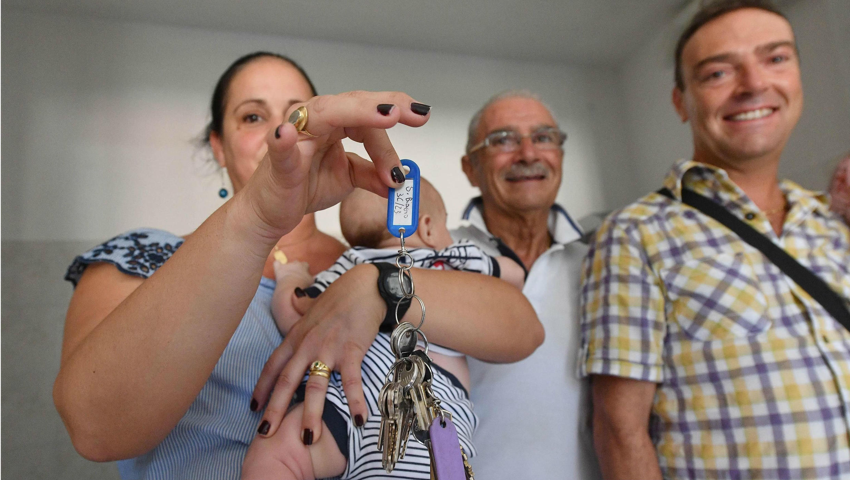 Una de las familias desalojadas tras el derrumbe del puente Morandi recibe una de las viviendas temporales entregadas por el Gobierno. Génova, Italia. 20 de agosto de 2018.