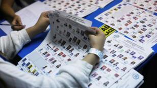 Los trabajadores electorales examinan las papeletas mientras cuentan los votos en Ciudad de Guatemala, Guatemala, después de la primera vuelta de las elecciones presidenciales, el 16 de junio de 2019.