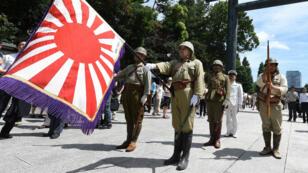 Des hommes en uniforme de l'armée impérialiste japonaise devant le sanctuaire controversé Yasukuni, à Tokyo.