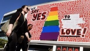"""Des Australiens passent devant une affiche défendant le """"oui"""" au vote sur le mariage gay, à Sidney le 14 novembre 2017."""