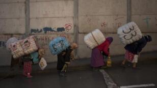 نسوة يعملن حمالات بين جانبي الحدود التي تفصل المغرب عن أسبانيا بسبتة، 26 ديسمبر 2014