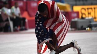 العداء الأميركي كريس كولمان يلف علم بلاده بعد تتويجه بطلا لسباق 100 م في بطولة العالم لألعاب القوى في الدوحة في 28 أيلول/سبتمبر 2020.