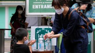 زوار يعقمون أيديهم لمنع تفشي وباء كوفيد-19 قبل دخول مدينة ملاه في طوكيو في 13 تموز/يوليو 2020