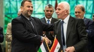 رئيس وفد فتح عزام الأحمد (يمين) وصالح العاروري رئيس وفد حماس يتصافحان بعد توقيع الاتفاق في القاهرة في 12 أكتوبر