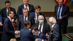 Leader of ruling Law and Justice (PiS) party Jaroslaw Kaczynski, wearing a mask, talks with ministers in parliament