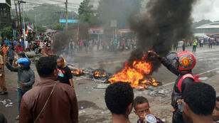 Des gens brûlent des pneus sur une route à Manokwari, capitale de la région ouest de la Papouasie, le 19août2019.