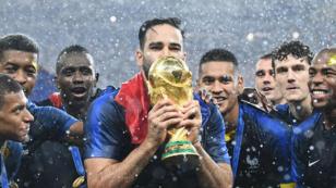 Adil Rami embrassant le trophée du Mondial après la victoire contre la Croatie (4-2), en juillet 2018.