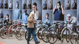 Una mujer pasa junto a una exhibición de fotos en el exterior del Royal Melbourne Hospital el 20 de octubre de 2020