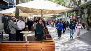 People walk along a pedestrian street past an open bar in downtown Santiago
