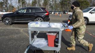 عنصر من الحرس الوطني الأميركي يدفع عربة عليها حقن للقاح موديرنا المضاد لكوفيد-19 في مدينة لندنديري في ولاية نيو هامشر (شمال شرق) في 4 شباط/فبراير 2021.